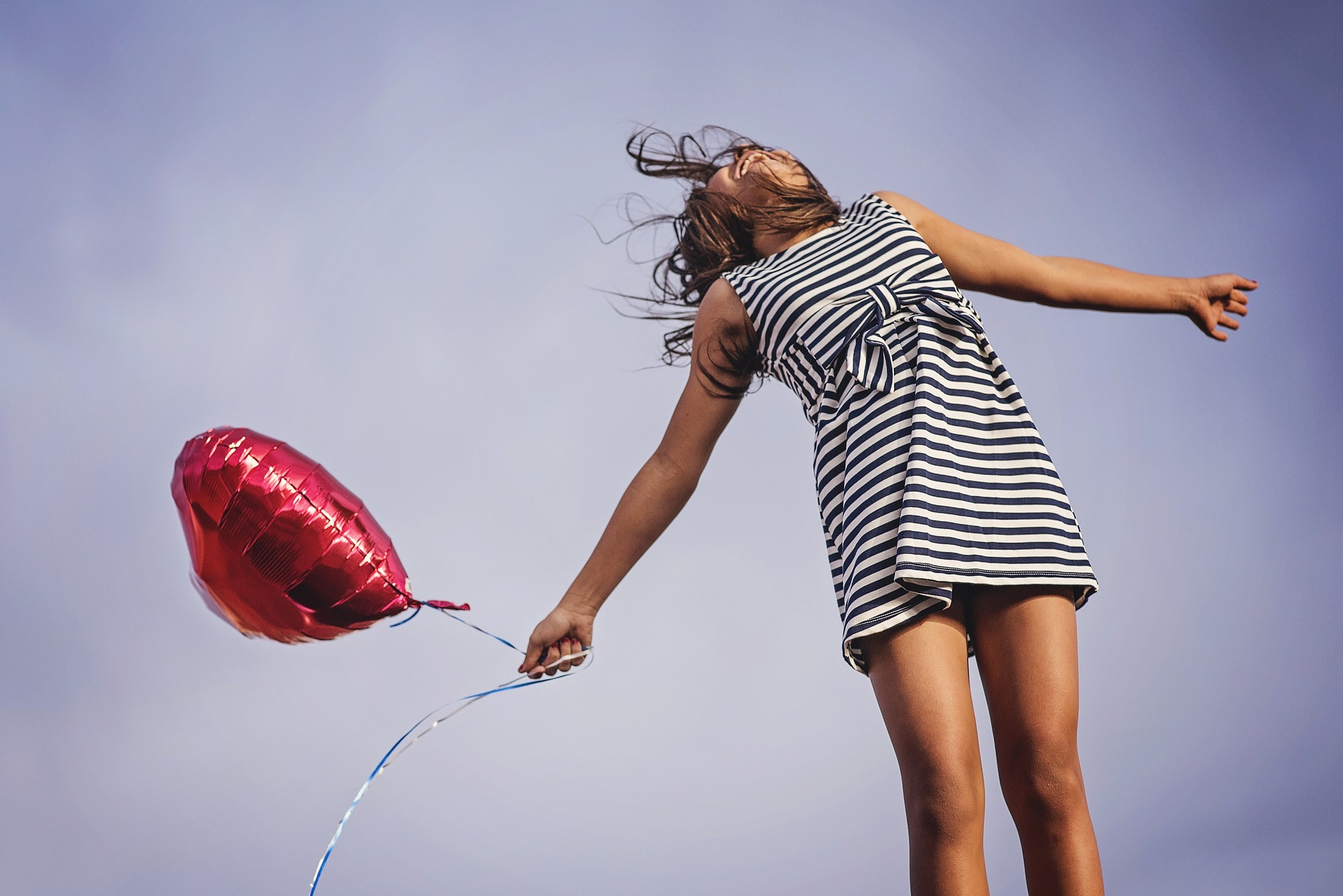 Woman Jumping with Heart Balloon